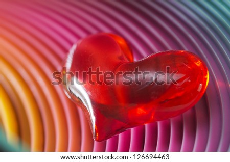 Atmospheric moody image of a glowing red Valentines heart in darkness with a spiralled tube effect background for a dramatic Valentines Day greeting card - stock photo