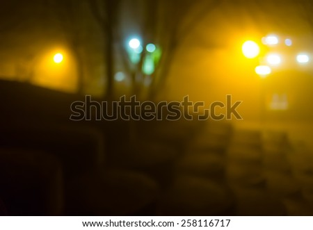 Atmospheric night scene in a foggy city park illuminated by street lights (diffused, toned). Dreamy cityscape. - stock photo