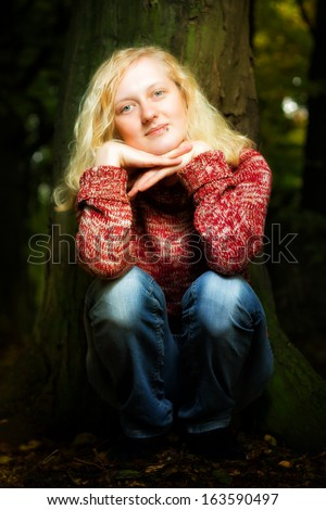 Atmospheric portrait of a charismatic young blond woman sitting outdoors in the darkness with her chin resting on her hands smiling at the camera - stock photo