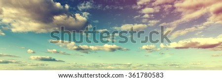 Atmospheric toned panoramic skyscape with colorful clouds at sunset or sunrise in a nature or weather banner - stock photo