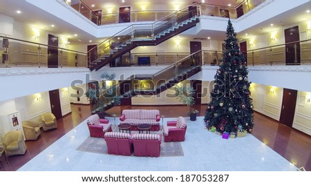 Atrium with armchairs, couches and Christmas tree in hotel. Aerial view - stock photo