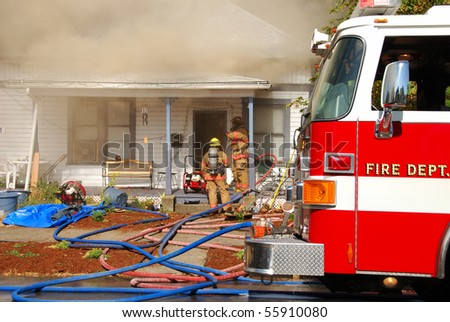 Attack and Backup lines in front of a Single family dwelling on fire on SE Mill Street in the Mill Pine Historic District of Roseburg Oregon. - stock photo