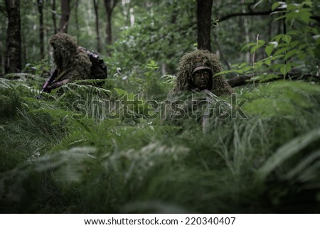 Attack of camouflaged soldiers with assault rifles in forest - stock photo