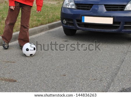 Attention child with the ball on the street - stock photo
