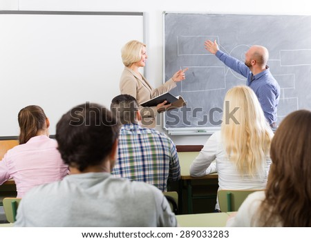 Attentive adult students with female teacher at training session for employees - stock photo