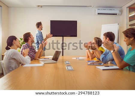 Attentive business team applausing after a conference in the office - stock photo