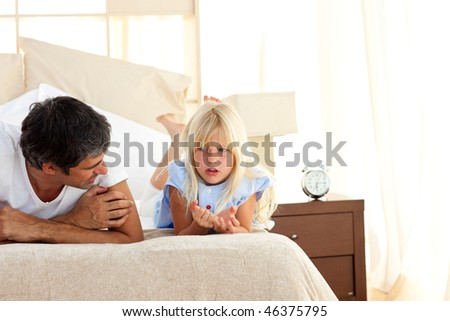 Attentive father talking with his daughter lying on bed - stock photo