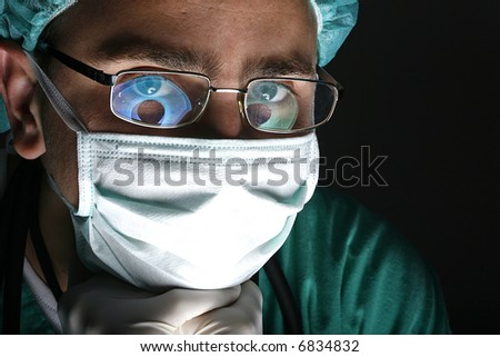 attentive look of working surgeon in operation room - stock photo