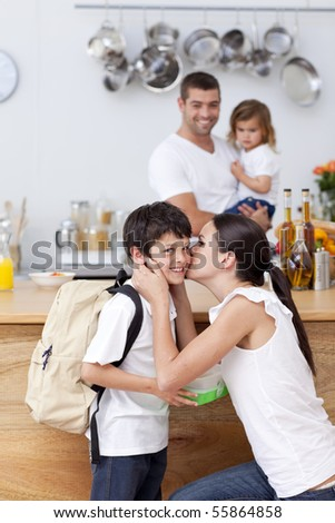 Attentive mother giving school lunch to her son in the kitchen - stock photo