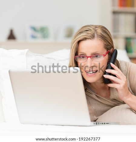 Attentive woman wearing glasses talking on her mobile phone as she lies on her sofa reading information on the screen of her laptop - stock photo