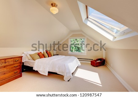 Attic modern bedroom with white bed and skylight and beige walls and carpet. - stock photo