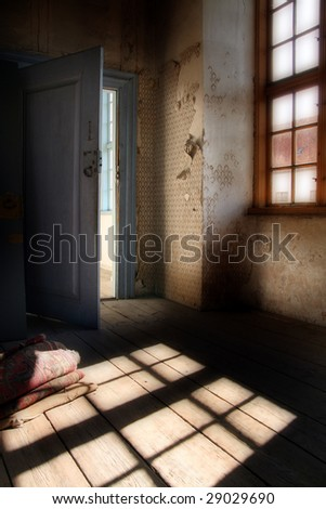 attic room in old manor house. Spooky interior with peeling walls and wallpaper - stock photo