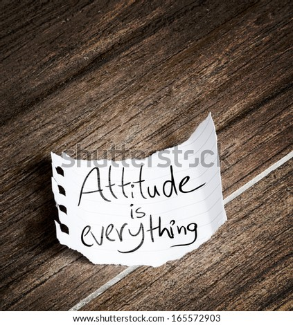 Attitude is Everything written on the paper on a wood background - stock photo