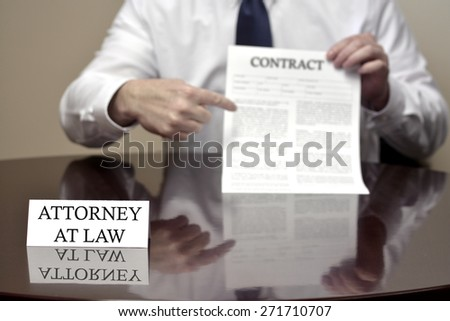 Attorney at Law sitting at desk holding Contract - stock photo