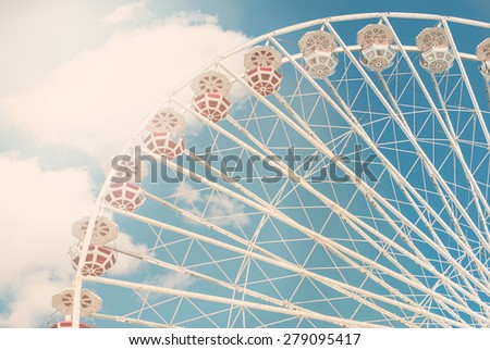 Attraction Ferris wheel against the blue sky with a few clouds on a sunny day - stock photo