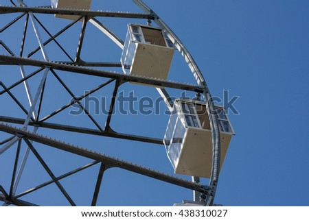 Attraction Ferris wheel in city amusement park. - stock photo