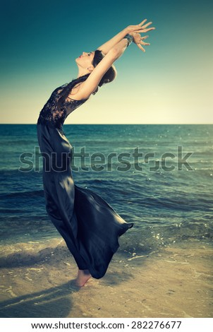 attractiv woman in elegant dress posing on the beach - stock photo