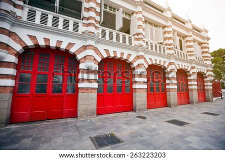 Attractive, accented brickwork facade and bright red painted garage doors of a fire station in singapore. - stock photo