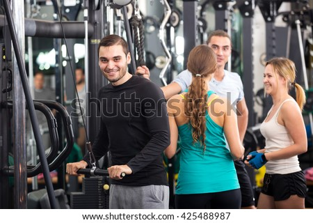 Attractive active young people having weightlifting training in health club - stock photo