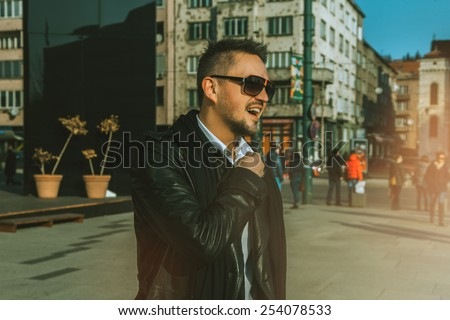 Attractive adult male model looking away on the street at daytime - stock photo