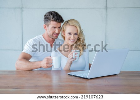 Attractive affectionate couple sitting close together drinking coffee and reading their social media or morning news on a laptop computer - stock photo