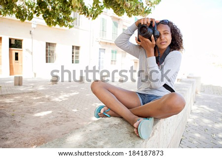 Attractive african american black teenager girl sitting on the bench of a village street, using a slr digital camera taking photographs on a summer holiday. Photography student and tourism lifestyle. - stock photo