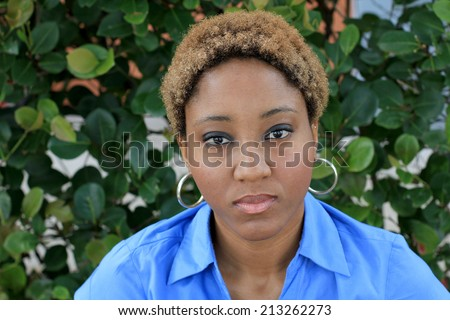 Attractive African American Business Woman Looking Seriously at the Camera Wearing a Blue Shirt with Black and Blonde Hair - stock photo