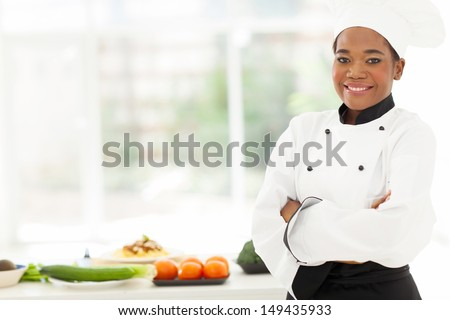 attractive african american female chef with arms folded in restaurant kitchen - stock photo