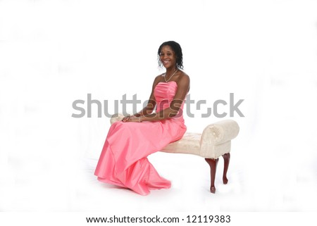 Attractive African American teenage girl wearing a pink strapless gown, sitting on an ivory bench against a white background. - stock photo