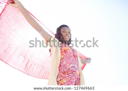 Attractive african-american woman holding a red fabric sarong up in the air against a bright blue sky while on vacation, smiling. - stock photo