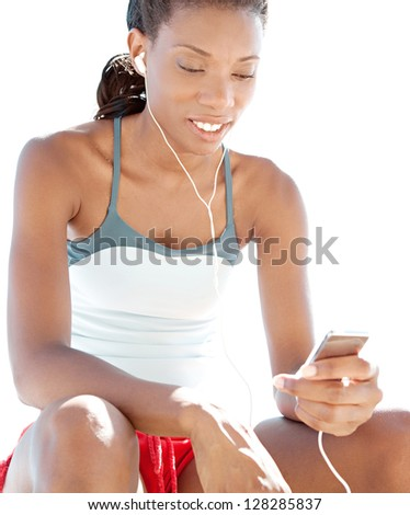 "Attractive ""african american"" woman listening to music with her mp4 player while having a break from exercising on a sunny day. - stock photo"