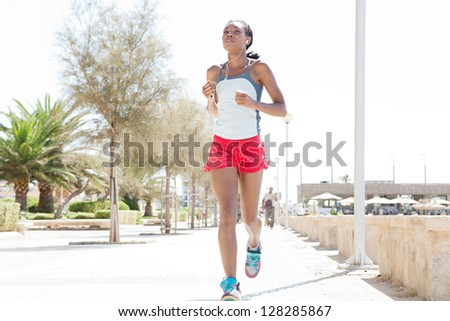Attractive african-american woman running and exercising in the city, listening to music with her ear phones on a sunny day. - stock photo