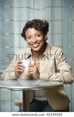 Attractive African-American woman sits at a table. She is holding a coffee cup and smiling towards the camera. Vertical shot. - stock photo