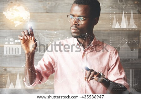 Attractive African businessman wearing glasses navigating futuristic interface looking at the screen with concentrated and serious expression while working on a project, making graphics and diagrams - stock photo