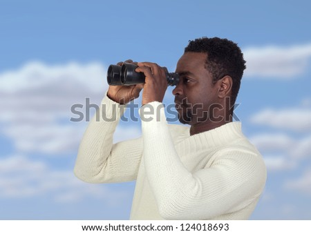 Attractive african man looking through binoculars with a blue sky of background - stock photo