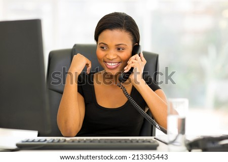 attractive african office worker talking on the phone - stock photo