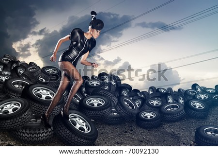 Attractive african woman running on tires on the cloudy sky - stock photo