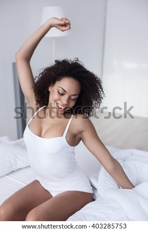 Attractive african woman stretching arms after sleeping - stock photo