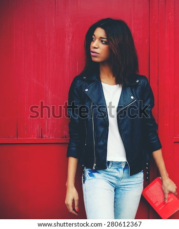 Attractive afro american female posing on red wall background in urban setting, young brunette woman holding book in the hand while strolling in the city at her recreation time, filtered image - stock photo