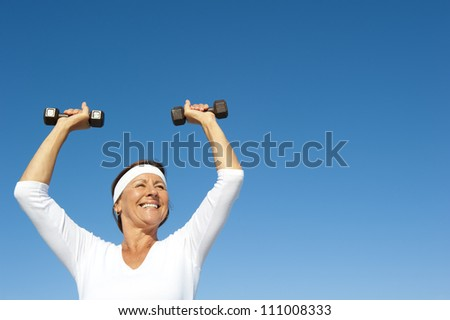 Attractive and active senior woman exercising with weights,  isolated with blue sky as background and copy space. - stock photo
