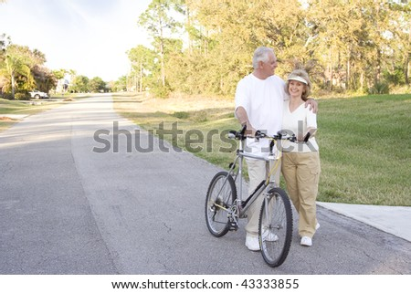 Attractive and fit seniors on bikes outdoors. - stock photo