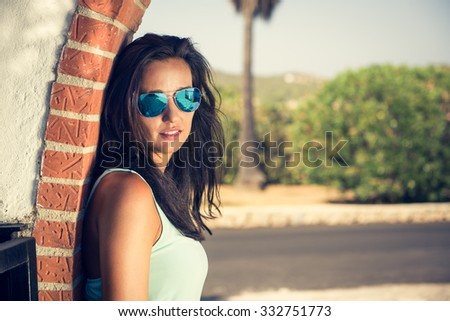 Attractive and good looking girl posing in modern, fashion clothing. Woman looking at the camera. Outdoor photo. - stock photo