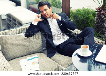 Attractive and handsome businessman using mobile phone, asian businessman having a phone talk, wealthy man talking on the smart phone seated in the terrace of modern lounge cafe at his work break - stock photo