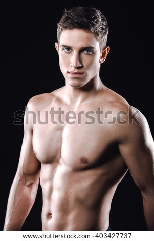 Attractive and muscular athlete. Studio shot of young shirtless sportsman on black background. Man looking at camera - stock photo