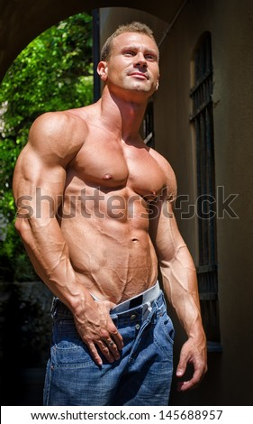 Attractive and muscular male bodybuilder shirtless in jeans smiling - stock photo