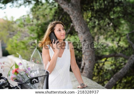 attractive and romantic young woman making phone call outdoor in summer holiday vacation  - stock photo