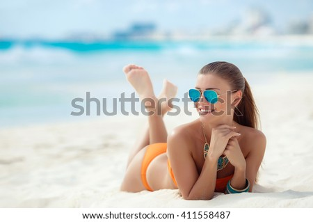 Attractive and sexy girl on the beach. Portrait of smiling young woman laying on sand by sea. long haired woman with flower in hair in bikini on tropical beach - stock photo