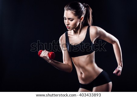 Attractive and slim woman. Studio shot of young sporty woman on black background. Woman training with dumbbell - stock photo