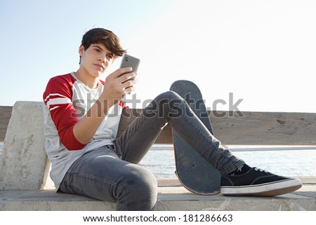 Attractive and thoughtful teenager boy relaxing with a skateboard and sitting down on a bench by the sea, holding and using a smartphone during a sunny day. Outdoors lifestyle. - stock photo