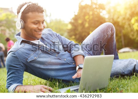 Attractive Arabian student is relaxing on lawn - stock photo